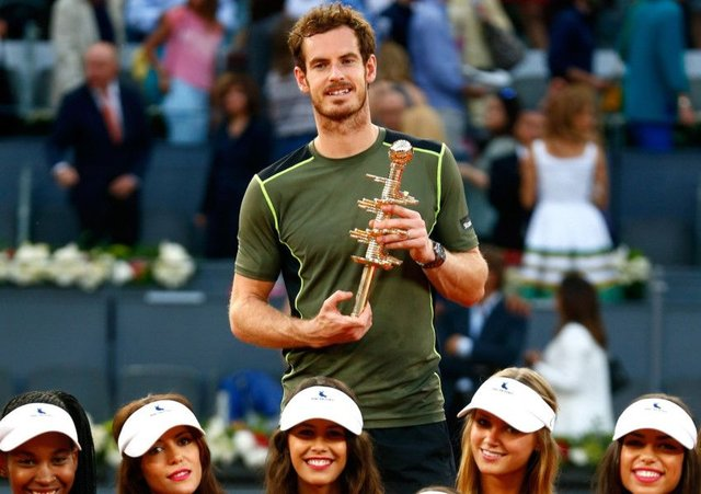Andy Murray  surrounded by the events model ball girls  holds the Madrid trophy. Picture: Getty