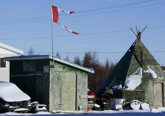 A tattered Canadian flag flies over a building in Attawapiskat, an indigenous area of Ontario, Canada. Picture: AP