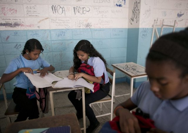 Maria Arias, centre, works with a  classmate. The youngster has been robbed at gunpoint in school. Picture: AP