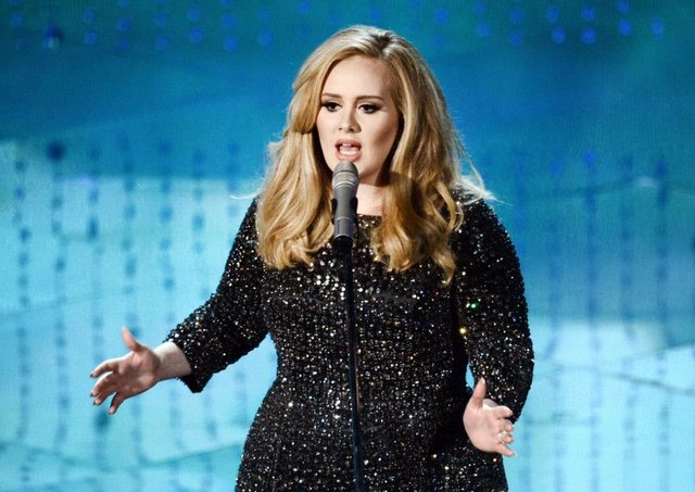 Adele stuns fan on stage with a kiss on the lips. Picture: Kevin Winter/Getty Images