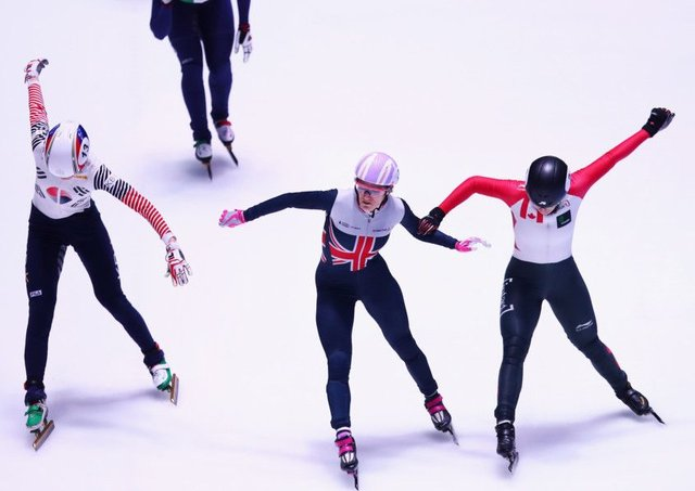 Elise Christie, centre, crosses the line first with Marianne St-Gelais, right, in second. Photograph: Dean Mouhtaropoulos/Getty