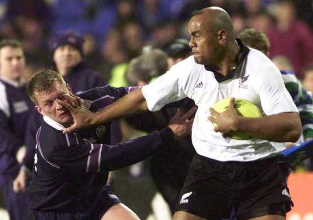 All Black Jonah Lomu plants his hand in the face of Scotland's Cameron Murray during the Second Test at Eden Park, Auckland in July 2000. Picture: Getty