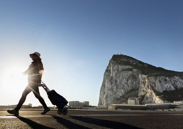 A woman walks on the Spanish side of the border between Spain and the British overseas territory of Gibraltar with the iconic Rock of Gibraltar in the background. Picture: AP Photo/Daniel Ochoa de Olza