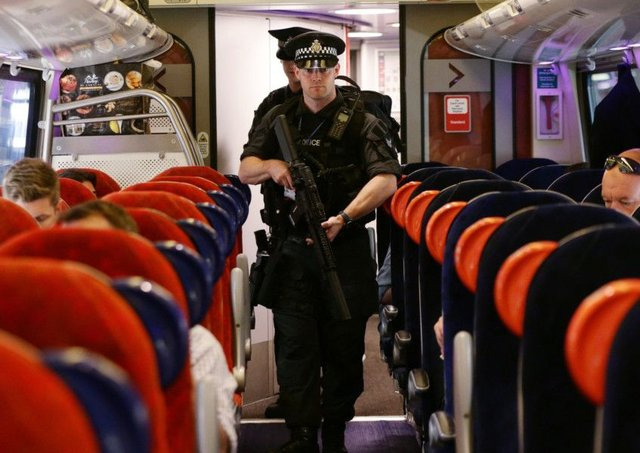Armed British Transport Police Specialist Operations officers on board a Virgin train to Birmingham New Street. Picture: PA