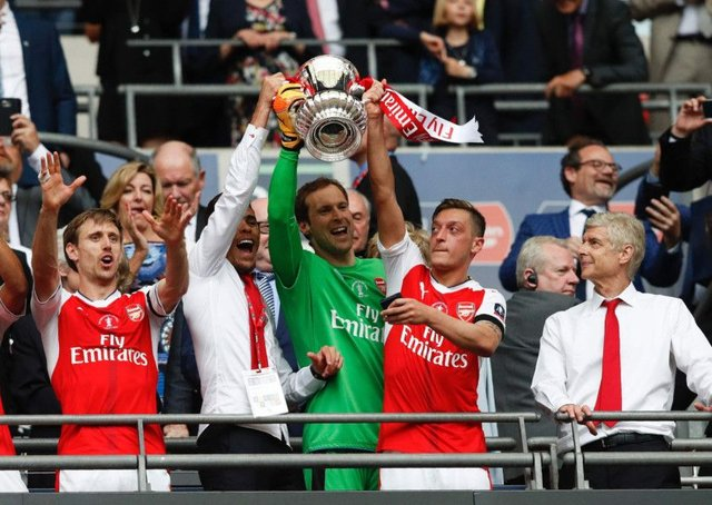 Arsene Wenger looks on as Gabriel, goalkeeper Petr Cech and Mesut Ozil lift up the FA Cup. Photograph: Adrian Dennis/AFP/Getty