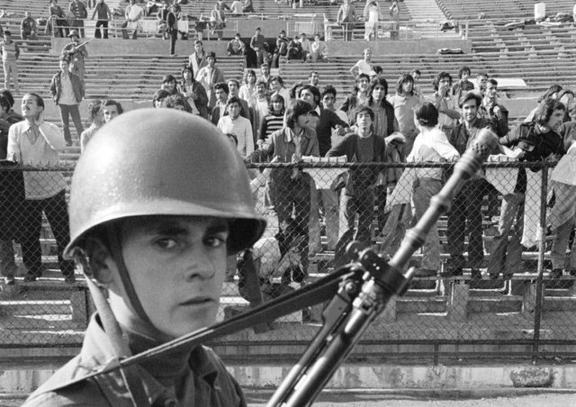 A soldier guards prisoners at Chile's National Stadium in 1973, shortly after the country endured a violent political coup. Picture: Bettmann Archive