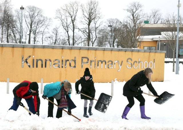 Parents, teachers and the local community of Larbert in Scotland begin clearing the grounds of Kinnaird Primary School, as the cold weather continues around the country. Picture: Andrew Milligan/PA Wire