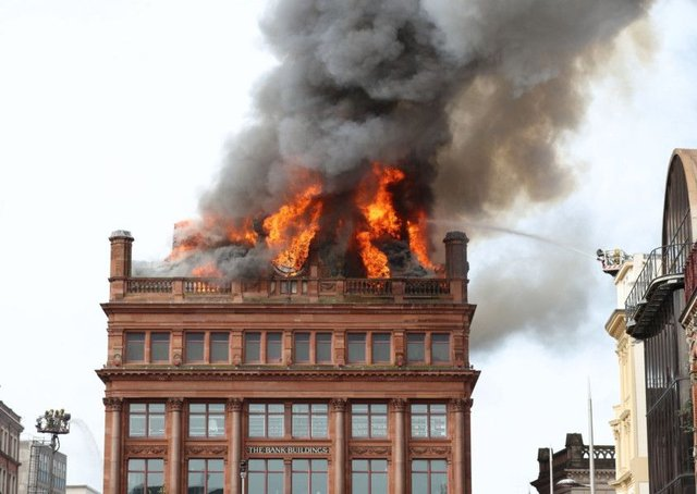 A firefighter trains a hose on a major blaze which has broken out at the Primark store in Belfast city centre. Picture: PA Wire