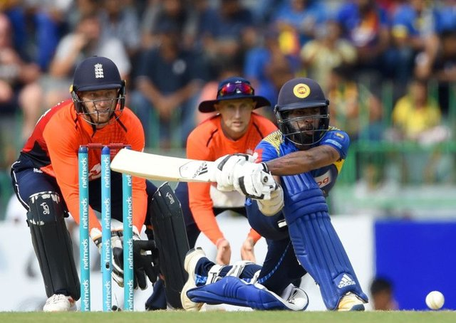 Sri Lanka's Niroshan Dickwella is watched by England wicketkeeper Jos Buttler as he plays a shot. Picture Ishara S Kodikara/AFP/Getty