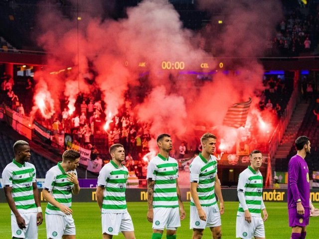 Celtic players line up for kick-off as supporters hold flares in the background. Picture: SNS