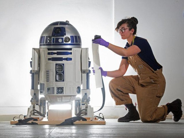 Jessie Giovane Staniland of V&A Dundee strikes a pose similar to Princess Leia in Star Wars as she takes a close look at the R2-D2 prop which will feature in its forthcoming robots exhibition.