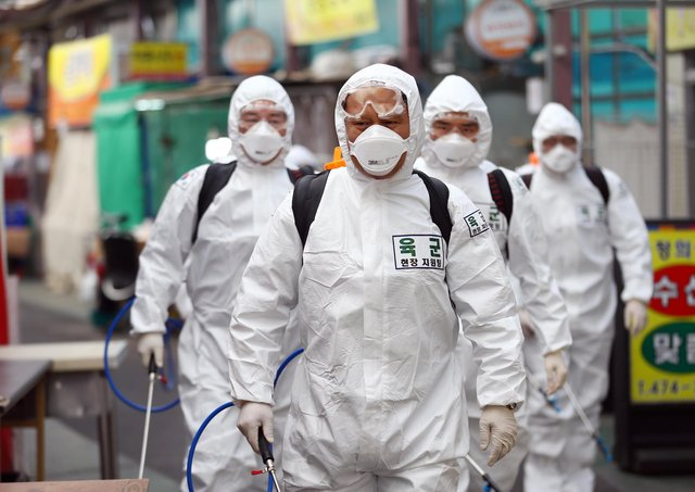 South Korean soldiers wearing protective clothing spray disinfectant as part of preventive measures against the spread of the Covid-19 coronavirus at a market in Daegu (Picture: Yonhap/AFP via Getty Images)