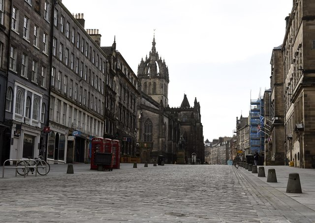 Many normally busy streets - such as Edinburgh's High Street - are now virtually empty as the coronavirus lockdown takes hold. Picture: Lisa Ferguson