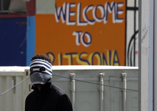 A young migrant wears an improvised mask at Ritsona refugee camp north of Athens as fear grows over the coronavirus pandemic (Picture: Thanassis Stavrakis/AP)