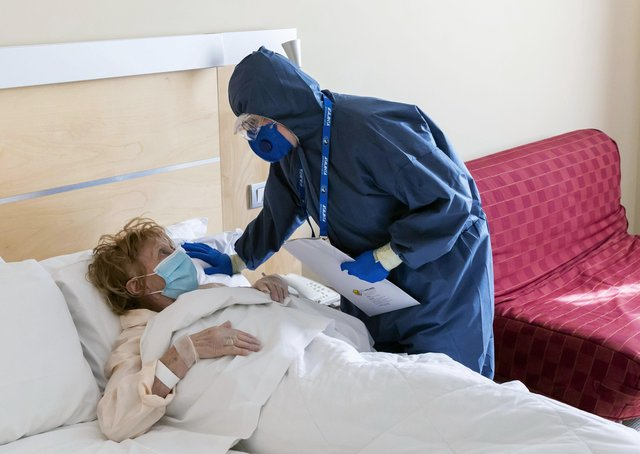 A nurse attends to a Covid-19 patient who has just arrived at a hotel in the village of Mozzo near Bergamo, Italy. (Picture: Marco di Lauro/Getty Images)