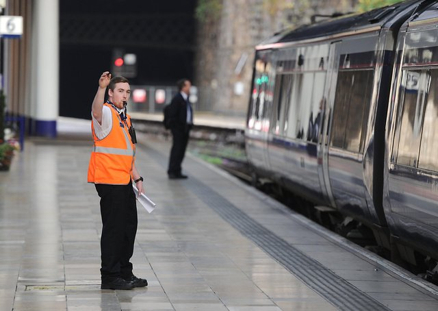 A conductor blows a whistle at Queen Street Station. Picture: John Devlin