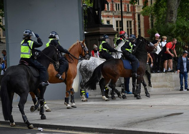 Bottles are thrown at mounted police as members of far-right groups gathered to guard statues in Parliament Square. Picture: Getty