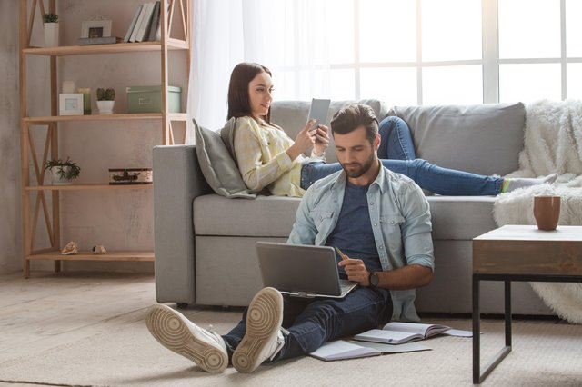 A couple indoors using a laptop. UK adults are now spending more than a quarter of their waking lives online