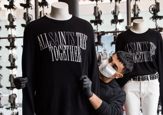 An All Saints staff member dresses a mannequin in Glasgow