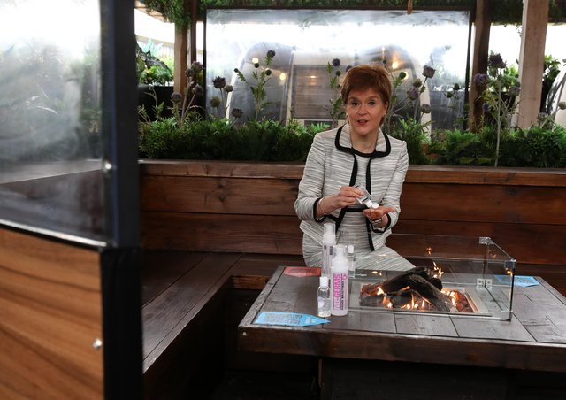 First Minister Nicola Sturgeon sits by a fire pit table during a visit to Cold Town House in Edinburgh's Grassmarket. Picture: Andrew Milligan - Pool/Getty Images