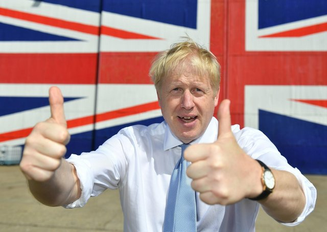 ISLE OF WIGHT, UNITED KINGDOM - JUNE 27: Conservative party leadership contender Boris Johnson poses for a photograph in front of a Union Jack on a wall at the Wight Shipyard Company at Venture Quay during a visit to the Isle of Wight on June 27, 2019 on the Isle of Wight, United Kingdom. Boris Johnson and Jeremy Hunt are the remaining candidates in contention for the Conservative Party Leadership and thus Prime Minister of the UK. Results will be announced on July 23rd 2019. (Photo by Dominic Lipinski - WPA Pool/Getty Images)