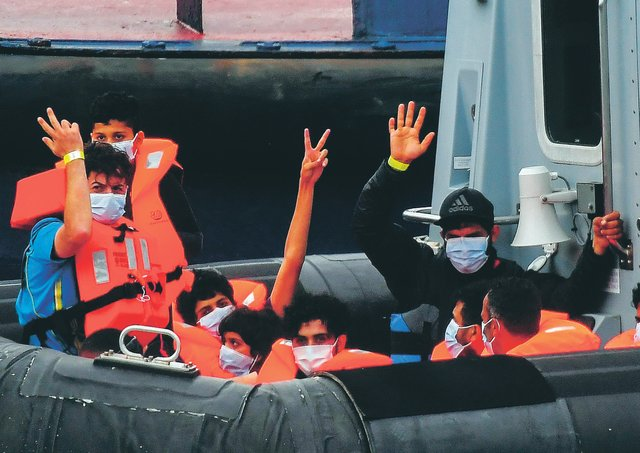 Migrants gesture as they arrive in port aboard a Border Force vessel after being intercepted while crossing the English Channel from France. Picture: Peter Summers/Getty Images
