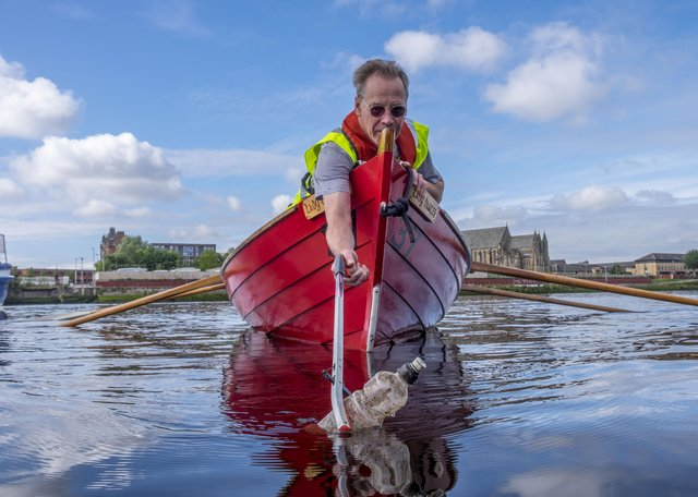 A volunteer fishes a bottle out of the River Clyde as part of Keep Scotland Beautiful's Upstream Battle clean-up campaign