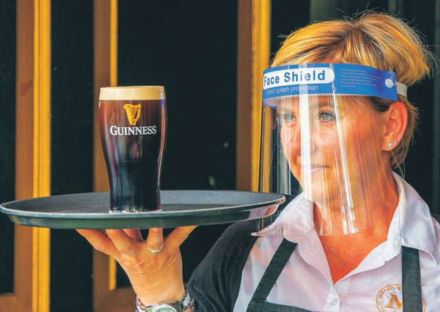 An employee wearing PPE (personal protective equipment) as she serves a customer's pint of Guinness. Picture: Paul Faith/AFP via Getty Images