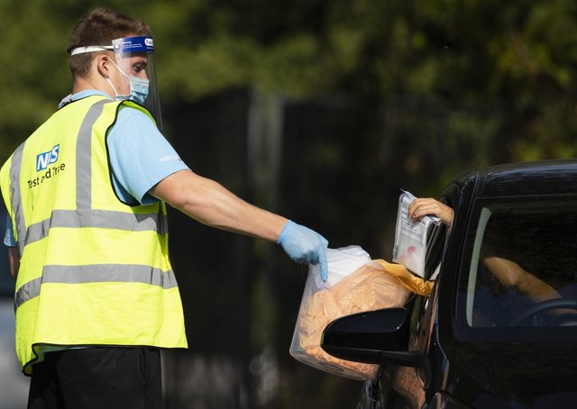 A worker collects a swab test from a member of the public at a Covid test site (Picture: Dan Kitwood/Getty Images)