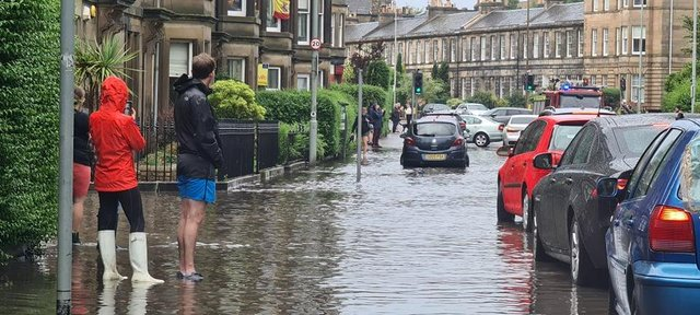 Pedestrians watching a fire engine driving slowly through the flooded streets of Stockbridge, Edinburgh, after heavy rainfall batters parts of the city.
