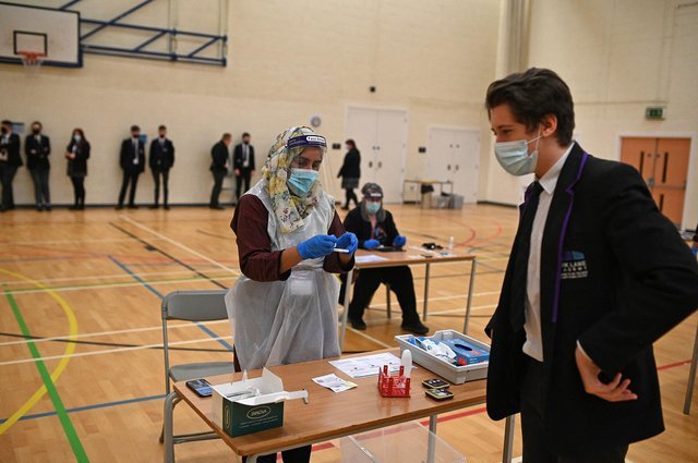 A member of staff wearing PPE processes a student's Innova lateral flow Covid-19 test, in the Sports Hall at Park Lane Academy in Halifax, northwest England.