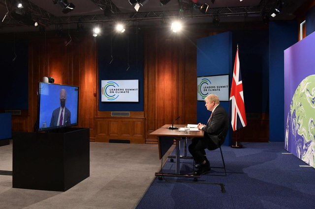 Boris Johnson and Joe Biden, on screen, take part in the opening session of the virtual summit on climate change organised by the US President (Picture: Justin Tallis/pool/AFP via Getty Images)