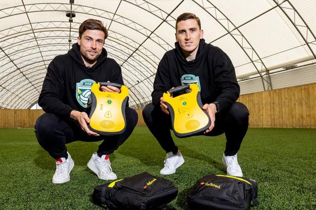 Hibs duo Lewis Stevenson and Paul Hanlon, via their Hanlon Stevenson Foundation, have handed over defibrillators to four local youth clubs. Photo by Alan Rennie