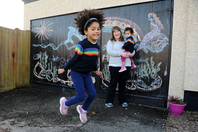 Larbert mum Christine Hilditch, a community artist, and five-year-old daughter Eilidh have been producing a series of colourful drawing to brighten up the day for passers-by - with a little help from baby sister Isla. Picture: Michael Gillen.