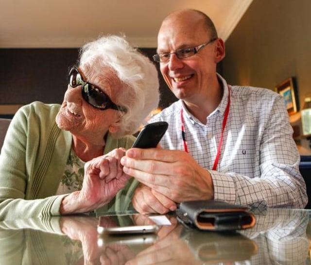 A Sight Scotland Veterans member of staff helping a veteran with new adaptive equipment.