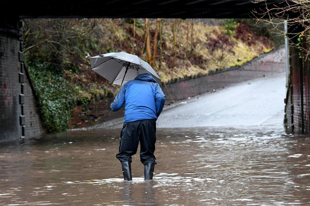 A man caught in a flooded area after a spell of heavy downpours picture: John Devlin/JPI Media