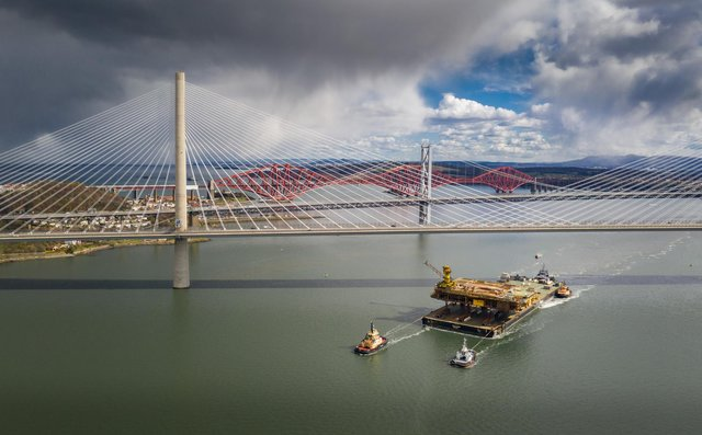 Aerial image of the Iron Lady barge with its cargo of a topside drilling platform for decommissioning being towed by Forth Ports tugs at the Forth Bridges into The Port of Rosyth on Sunday, April 11. Credit: Airbourne Lens