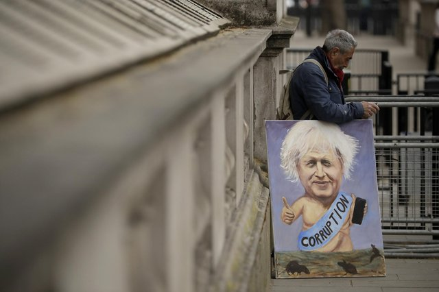 Political artist Kaya Mar holds one of his paintings of British Prime Minister Boris Johnson near the entrance to Downing Street, before Mr Johnson was driven past to go to the Houses of Parliament. Picture: AP Photo/Matt Dunham