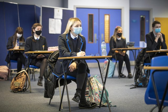 High school pupils have to wear masks in the classroom and maintain social distancing as they return to school part time.