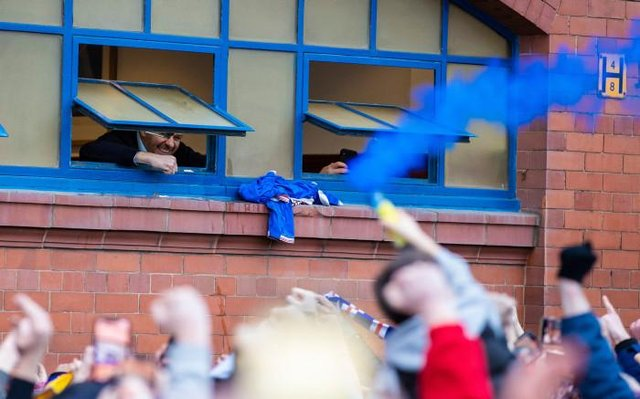 Rangers manager Steven Gerrard looks out of the dressing room window to greet supporters celebrating after the 3-0 win over St Mirren which effectively secured the Premiership title. (Photo by Craig Williamson / SNS Group)