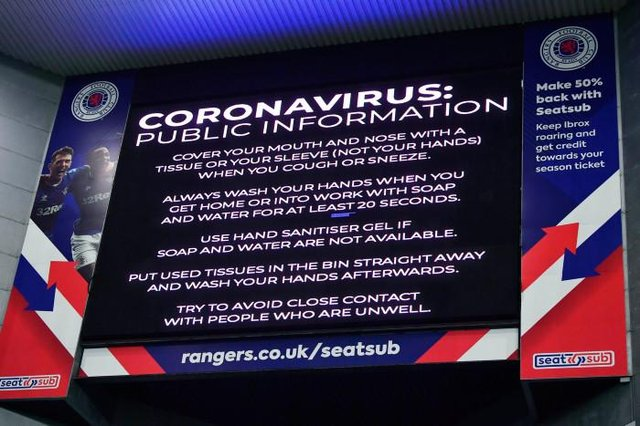 Coronavirus warning notices were prevalent last March - as seen here displayed on the big screens at Ibrox, days before the game was shutdown (Photo by Rob Casey / SNS Group)