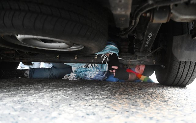One protester has wedged himself under the van to stop it driving away.