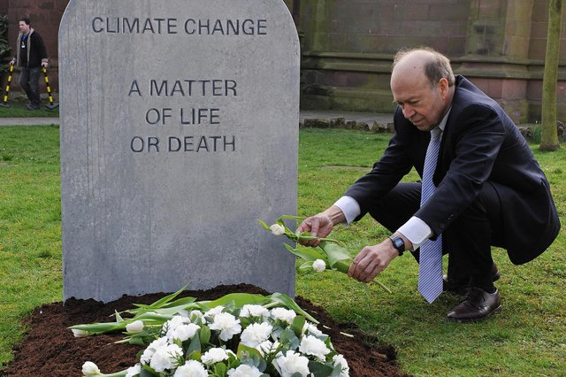 Climatologist Dr James Hansen lays flowers on a mock grave reading 'Climate change, a matter of life or death' in Coventry in 2009 (Picture: Carl de Souza/AFP via Getty Images)