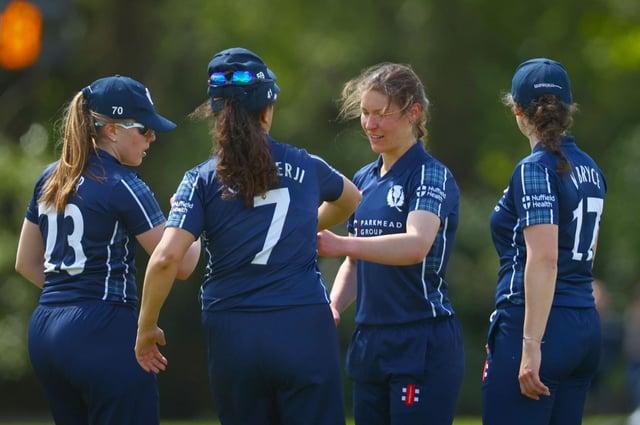 Katie McGill celebrates taking the third wicket for Scotland.
