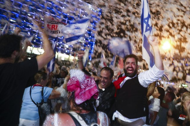 Israelis celebrate the swearing in of the new government in Tel Aviv on Sunday
