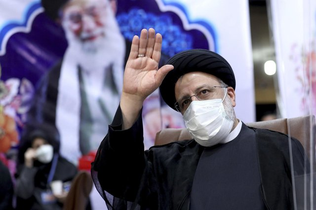 Ebrahim Raisi, head of Iran's judiciary, waves to journalists while registering his candidacy for the upcoming presidential elections at the Interior Ministry in Tehran (Picture: Ebrahim Noroozi/AP)