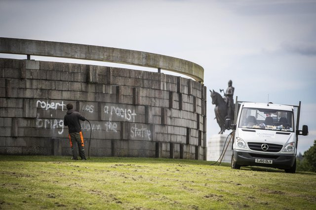 """Workers clean graffiti that reads """"Robert was a racist bring down the statue"""" at the Robert the Bruce rotunda in Bannockburn. PIC: Jane Barlow/PA Wire."""