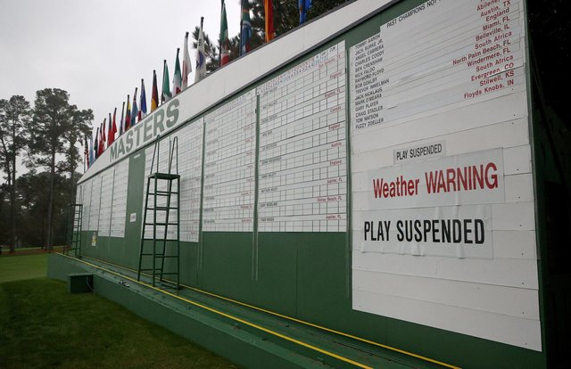 """The scoreboard is updated with a """"weather warning"""" and """"play suspended"""" sign during the first round of the Masters at Augusta National Golf Club. Picture: Rob Carr/Getty Images"""