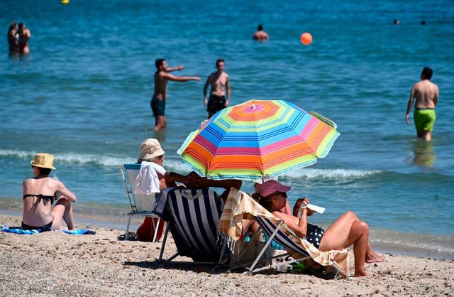 People enjoy the sun on a beach during a heatwave in Palavas-les-Flots, southern France, on June 23 as the country eases lockdown measures taken to curb the spread of the Covid-19 pandemic (Photo: PASCAL GUYOT/AFP via Getty Images)