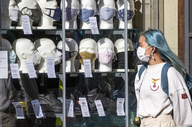 A woman wearing a protective face mask walks past a shop selling masks in Edinburgh city centre